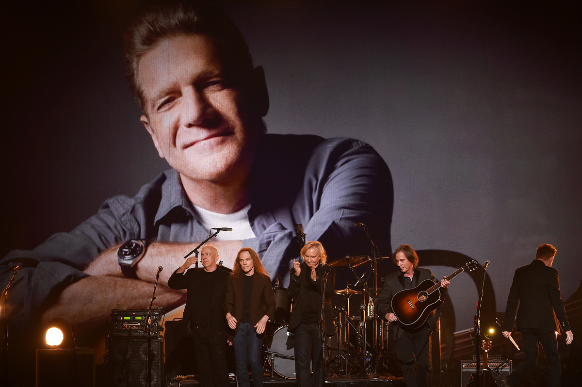 An image of the late Glenn Frey is displayed on a video screen as recording artists (L-R) Bernie Leadon, Timothy B. Schmit, Joe Walsh, Jackson Browne, and Don Henley perform onstage