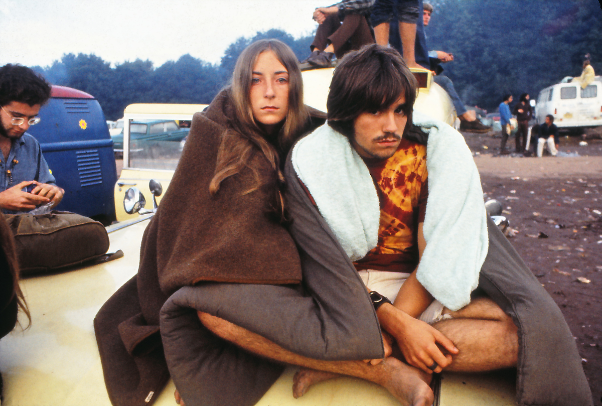 A young couple, sitting on a van, at the Woodstock Music Festival, New York, US, August 1969.