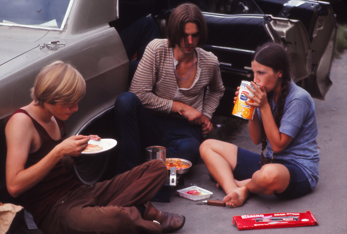 Young people relaxing and eating on their way to the Woodstock Music Festival, New York, US, August 1969.