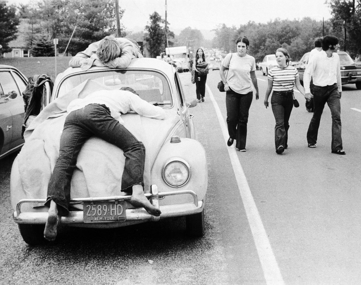 Two festival goers that found Woodstock too much lay passed out on the bonnet and roof of their Volkswagen Beetle.