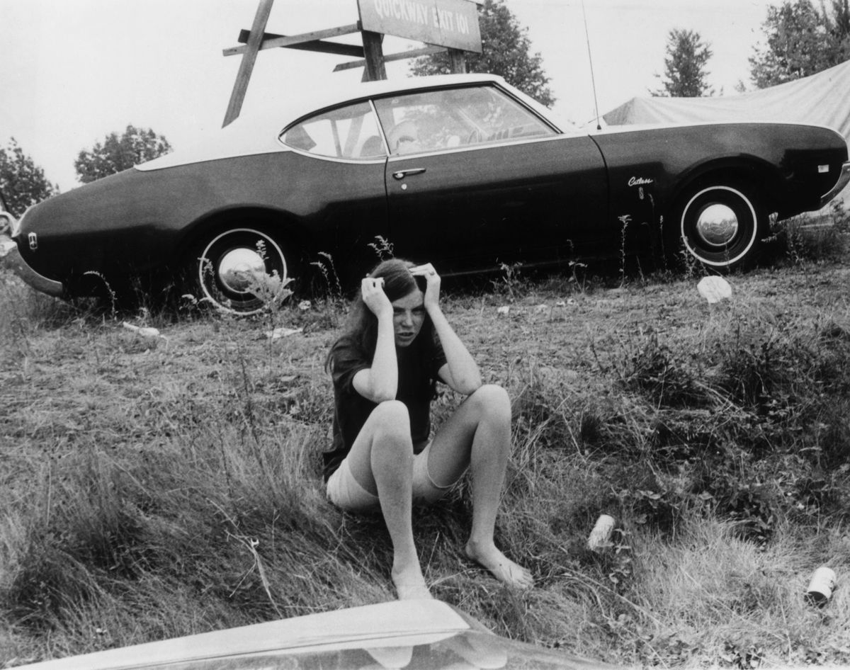 Pat McLean from Brighton Massachusetts, hangs her head as she waits beside a car at the Woodstock music festival.