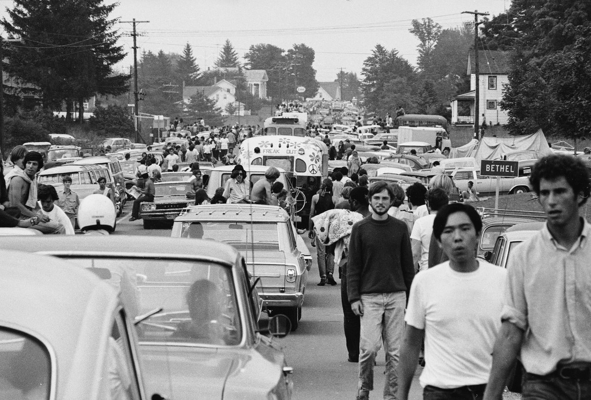 Members of the American youth subculture generally termed 'hippies' walk along roads choked with traffic on the way to the large rock conert called Woodstock, Bethel, New York, August, 1969. Sometimes likeminded motorists give them rides in or on their vehicles.