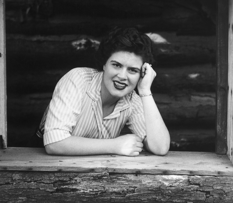Patsy is photographed leaning on one elbow in a wooden window sill