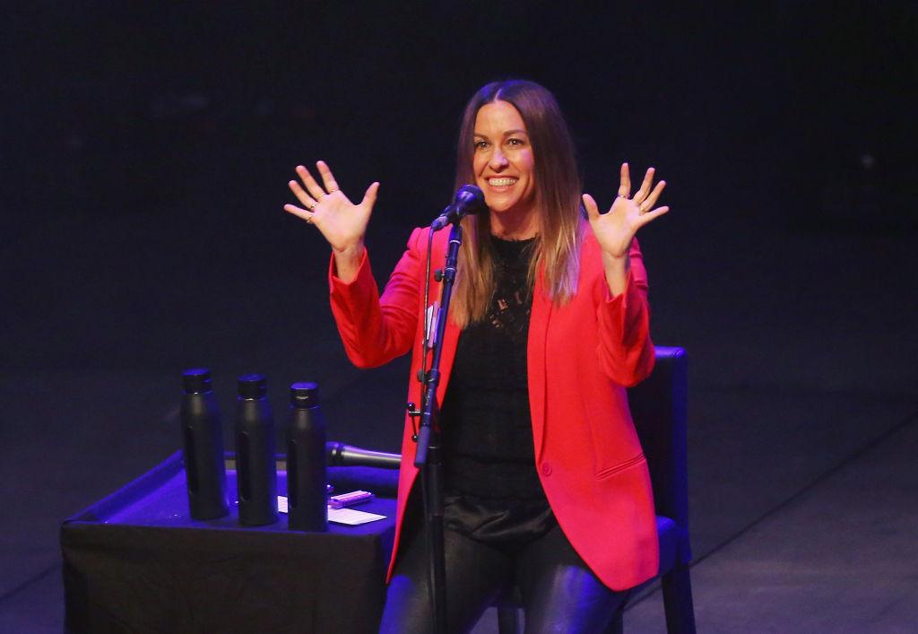 alanis morissette raising her hands on stage