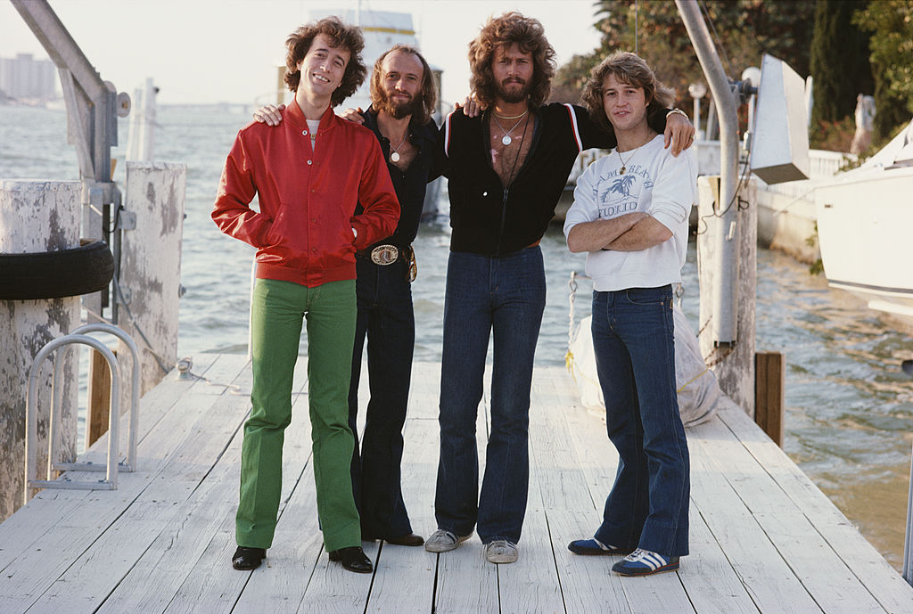 bee gees band members with their brother on a dock