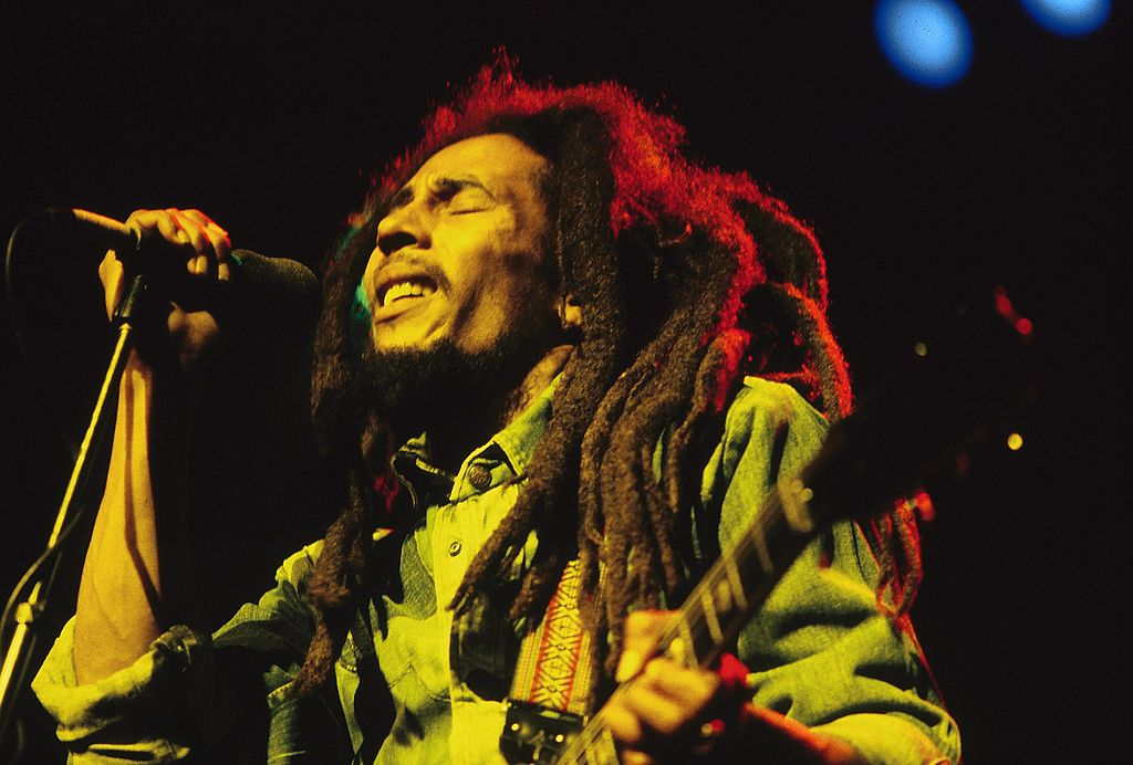bob marley performing live on stage under red, yellow, and green lights
