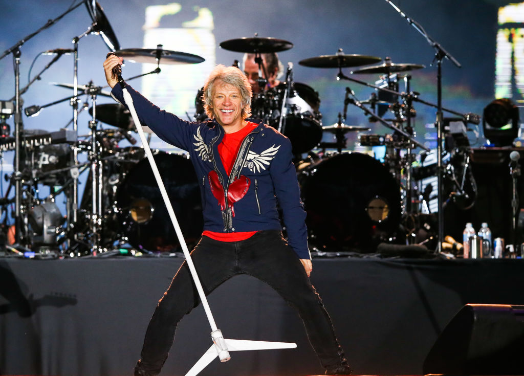 bon jovi performing on stage while picking up a microphone stand