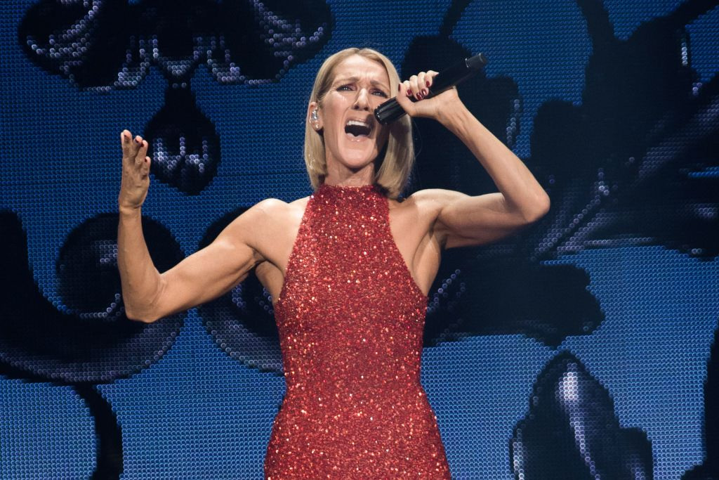 celine dion performing on stage in a red sequin dress