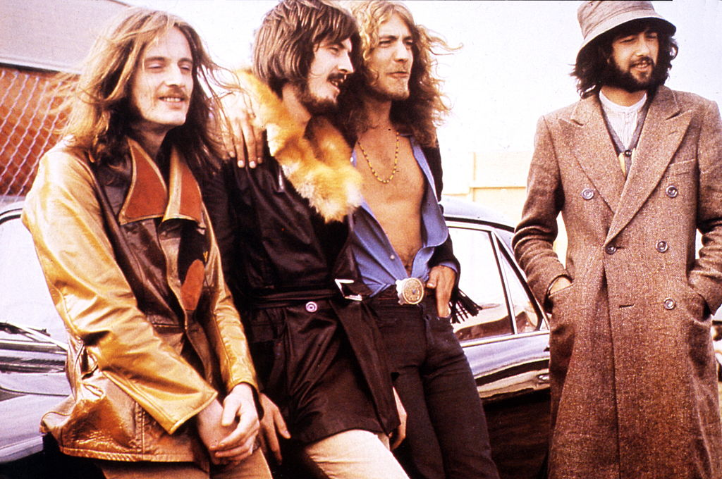 led zeppelin band members sitting in front of a car in 70s wardrobe