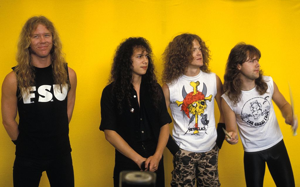 metallica standing in front of a yellow background