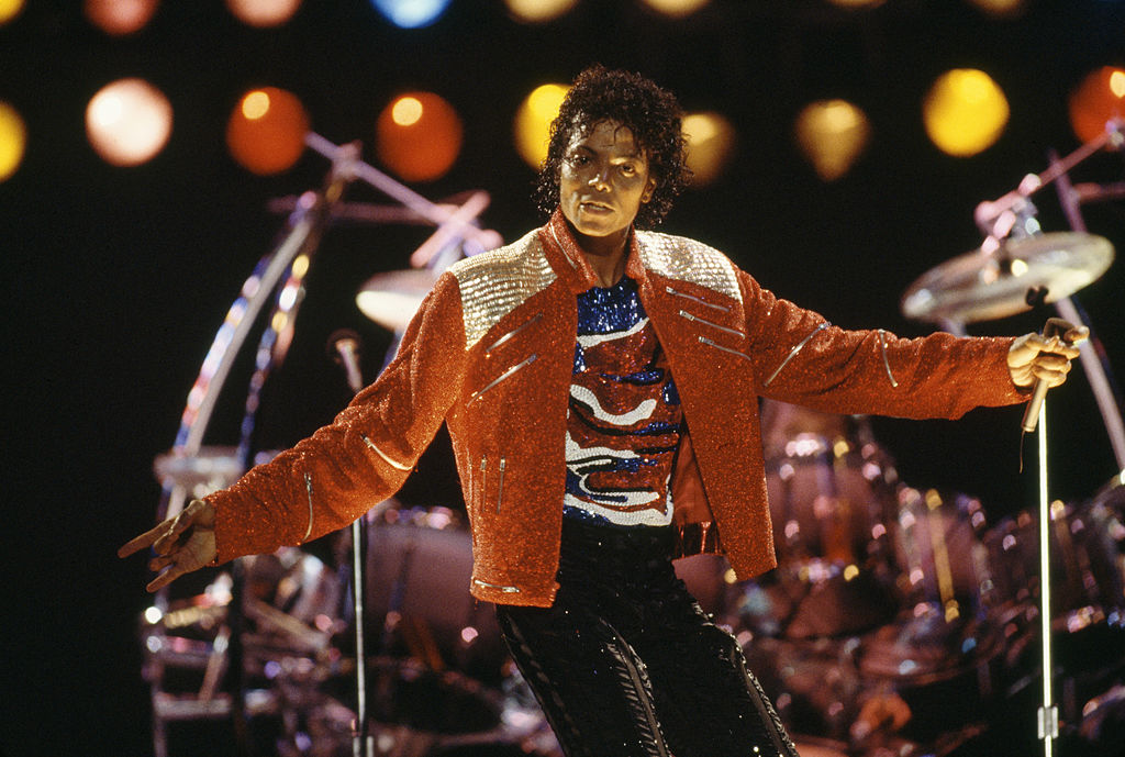 michael jackson performing on stage in a bedazzled red jacket in 1987