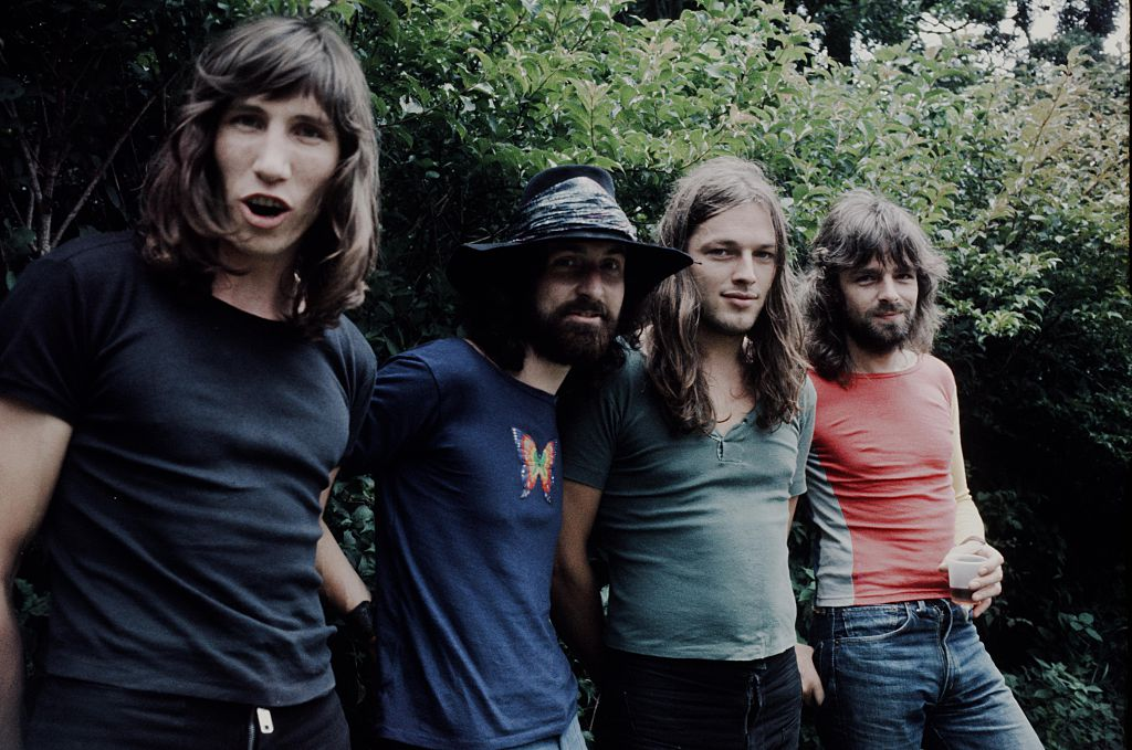 pink floyd band members in front of a plant outside