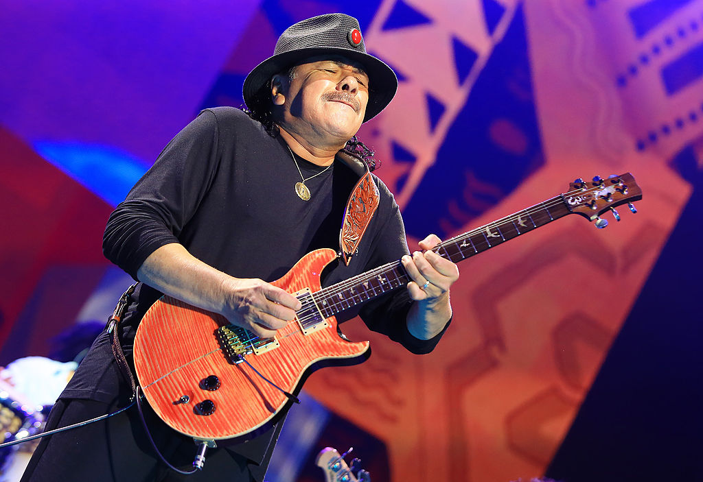 santana playing the guitar on stage and wearing a hat