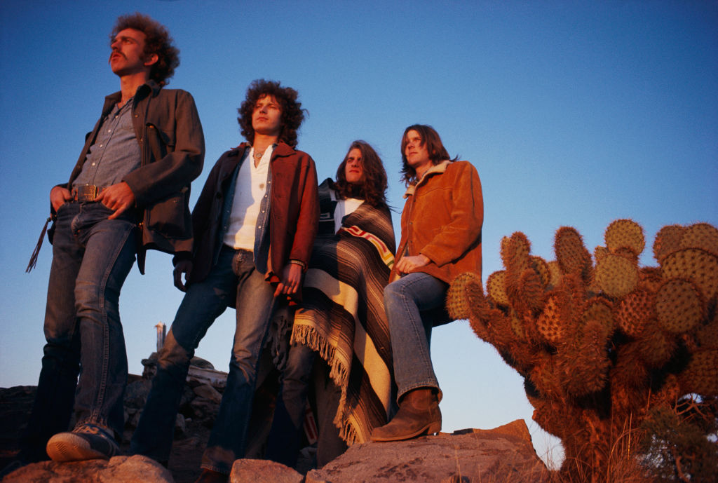 the eagles band members in desert valley posing next to a cactus