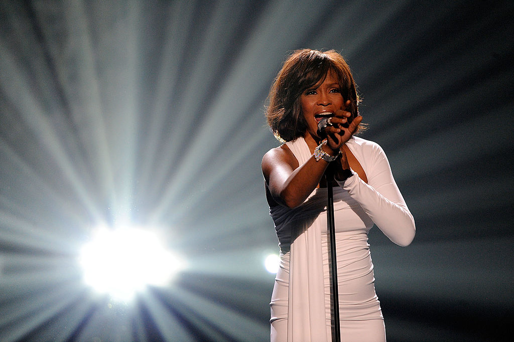 whitney houston singing on stage in a white dress and large spotlight