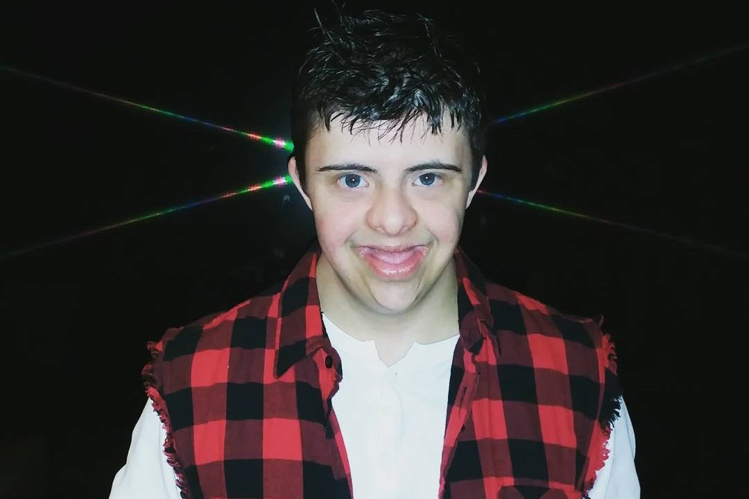 Anthony poses in front of a black background.