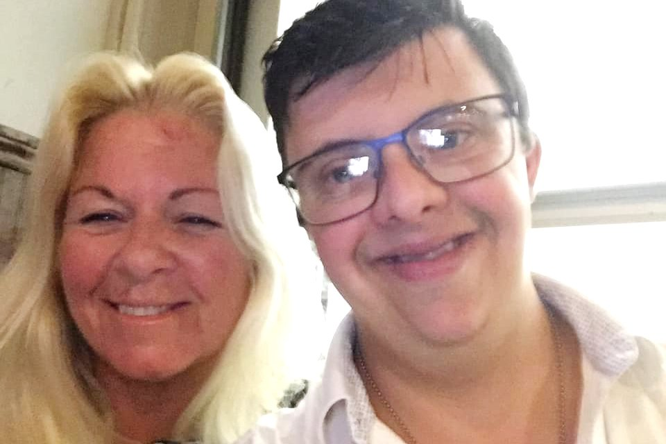 Anthony smiles while taking a selfie with his mother.
