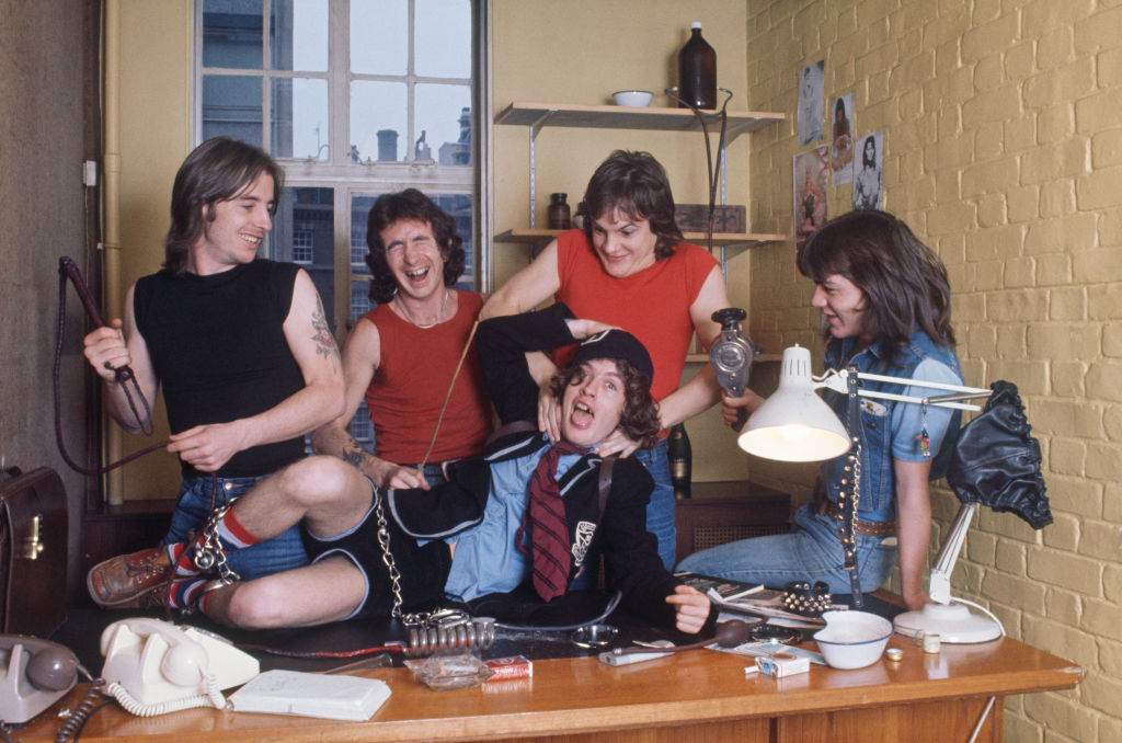 AC/DC posing for a picture on a desk