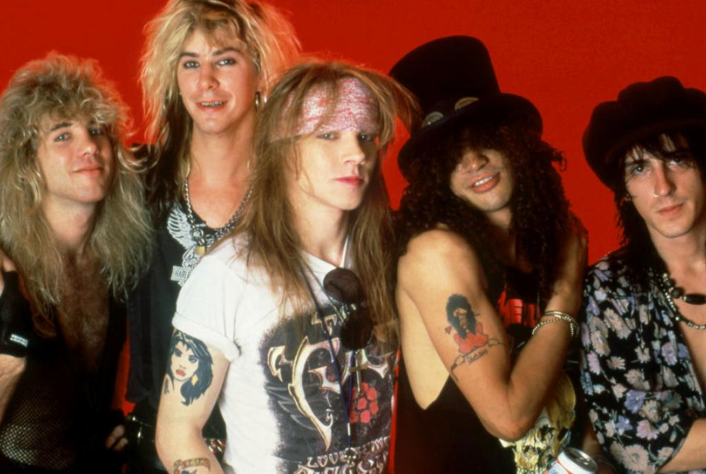 Guns N' Roses posing behind a red background