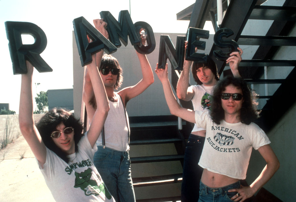 The Ramones holding up a sign of their band name