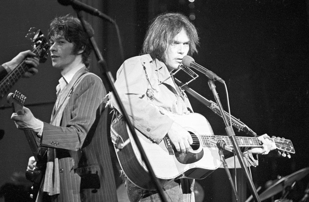 neil young and robbie robertson performing on stage